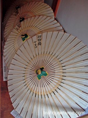 photograph of freshly made parasols drying in a temple hallway, Kyoto, Japan by A.E. Graves