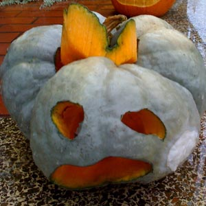 second face of jack o lantern carved into strangely lobed winter squash